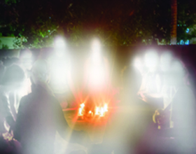 Image of a circle of people with candles in the middle of a table. there are bright shining see through people around them representing spirits.