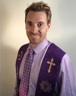 Picture of Rev. Mikel Lizarralde. He is wearing a purple shirt and a purple ministry stole with different religious traditions symbols on it.