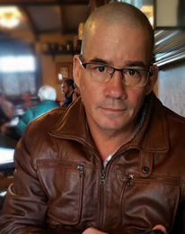 Rolando Gonzalez Sousa picture, a man with brown eyes wearing glasses with shaved head and wearing a brown leather jacket.