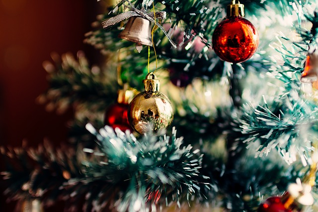 Image of a close up of a Christmas tree with read and gold balls on it.